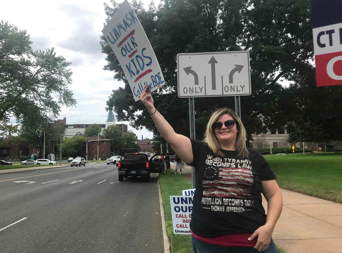 Among the protesters against mandates for masks and vaccinations at the state Capitol in Hartford on Saturday, Aug. 28, 2021, were at least two nurses holding out against the COVID-19 inoculations. Jennifer Semrow, of Middletown, a registered nurse at a rehabilitation facility in Connecticut, is shown along Capitol Avenue as cars drive by honking.