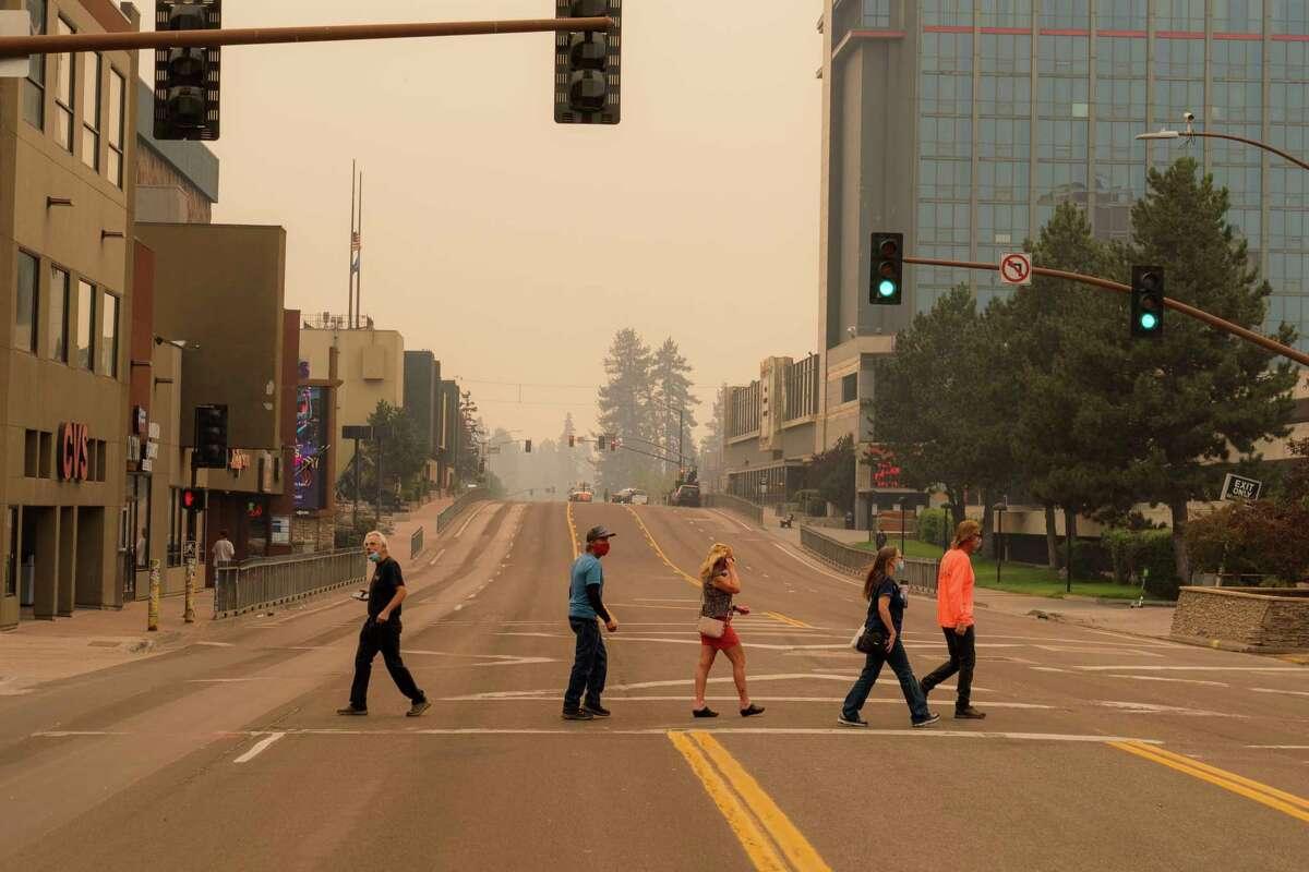 People cross Highway 50 in a nearly empty Stateline, Nev.