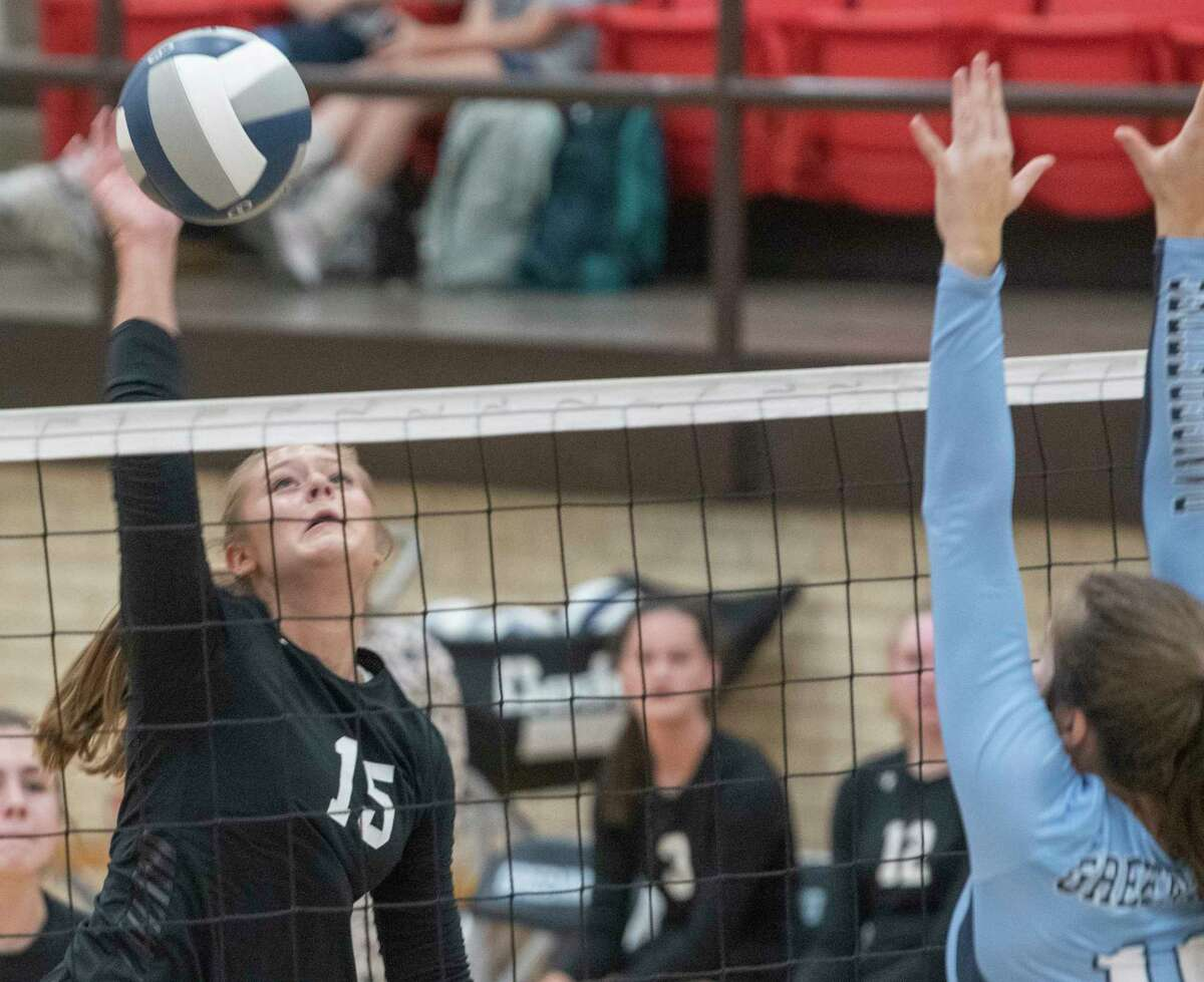 Midland Classical's Paytan Parham tries for a kill as Greenwood's Kaylee Jo Underwood goes for a block 08/31/2021 at Greenwood High School. Tim Fischer/Reporter-Telegram