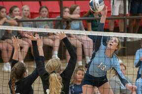 Greenwood's Kate Crunk tries for a kill as Midland Classical's Emma Westfall and Kenedi Carter try to block 08/31/2021 at Greenwood High School. Tim Fischer/Reporter-Telegram