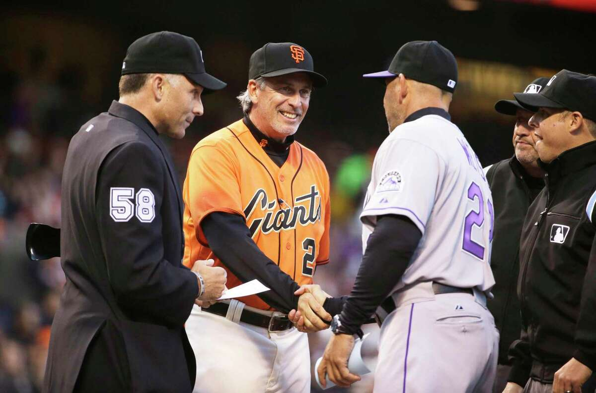San Francisco Giants bench coach Ron Wotus, center, shakes hands with Colorado Rockies manager Walt Weiss before the start of a baseball game Friday, April 11, 2014, in San Francisco. At left is home plate umpire Dan Iassogna. (AP Photo/Eric Risberg)