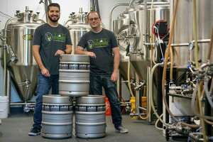 Black Laboratory Brewing company owners Tim Castaneda, left, and Jeff Weihe pose in the company's brewing room at the company's taproom at the intersection of North Hackberry and East Houston Street.