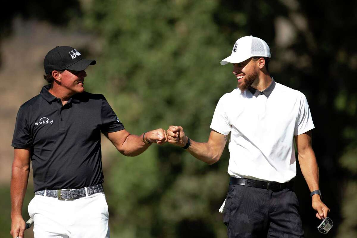 Phil Mickelson and Stephen Curry share a fist bump during the Safeway Open pro-am on Sept. 25, 2019 in Napa. Mickelson hit a flop shot over Curry at a charity event Friday at Harding Park.