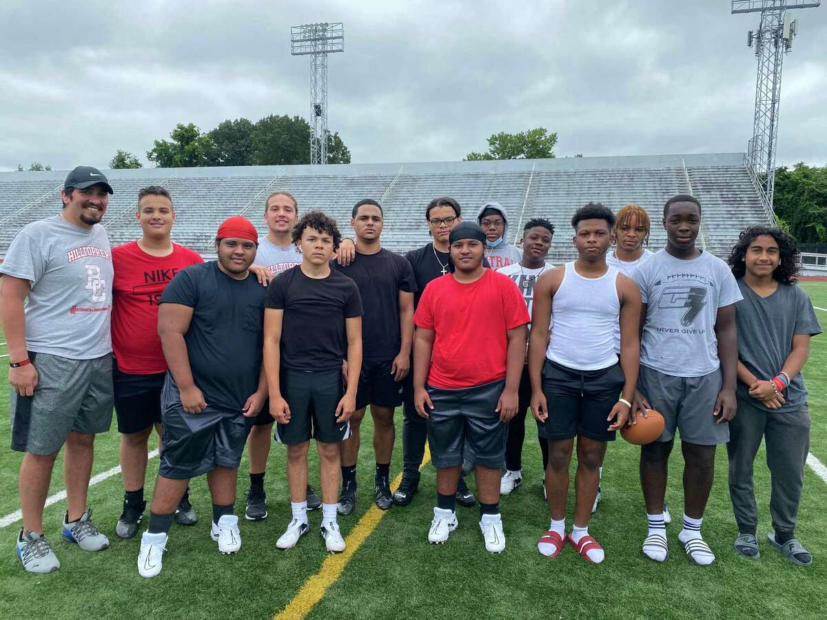 Bridgeport Central coach Tom Broschardt, left, poses with members of the football team at Kennedy Stadium on Thursday, August 5, 2021.