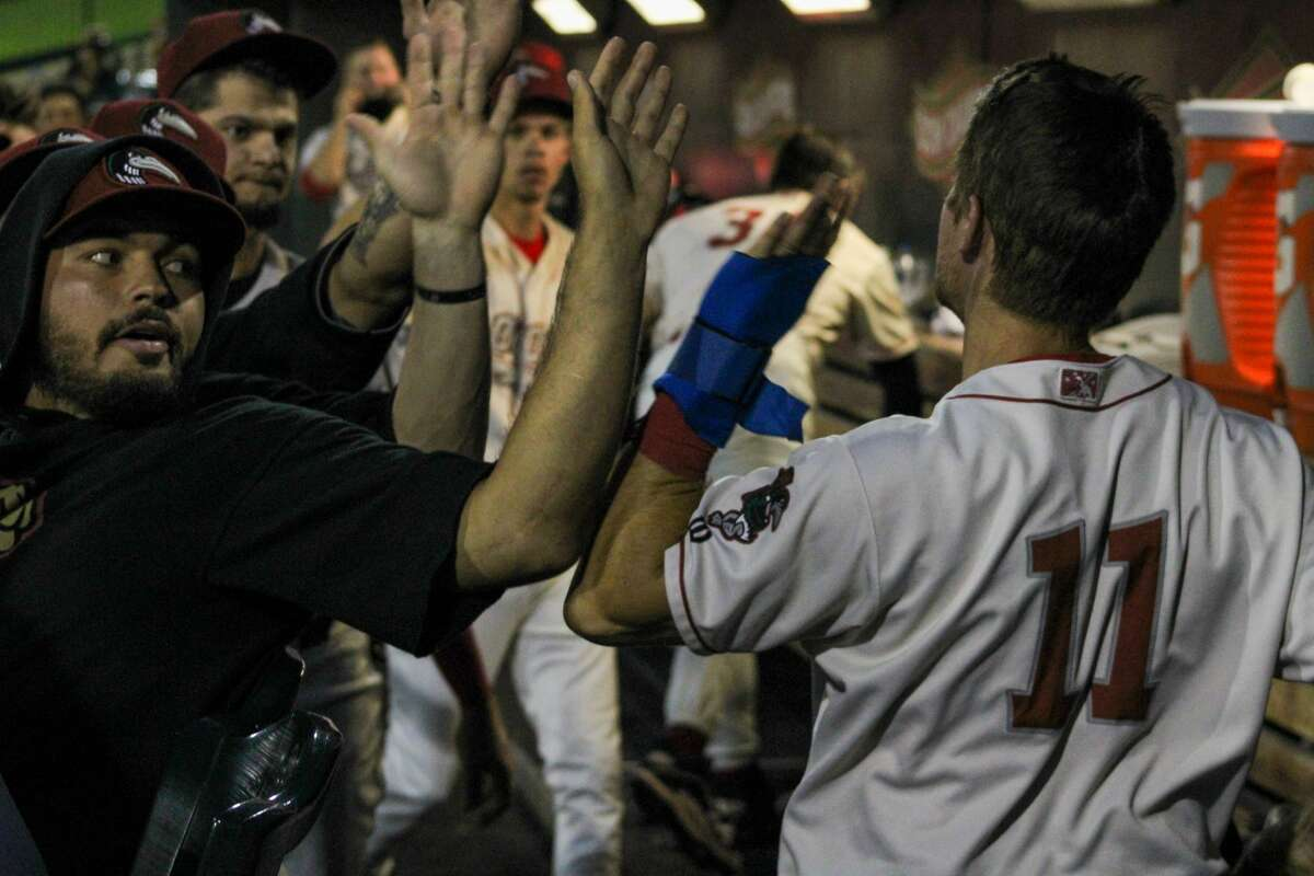 Loons left fielder Jonny DeLuca high-fives his teammates after scoring against Fort Wayne on Aug. 31 at Dow Diamond (Austin Chastain/austin.chastain@hearstnp.com)