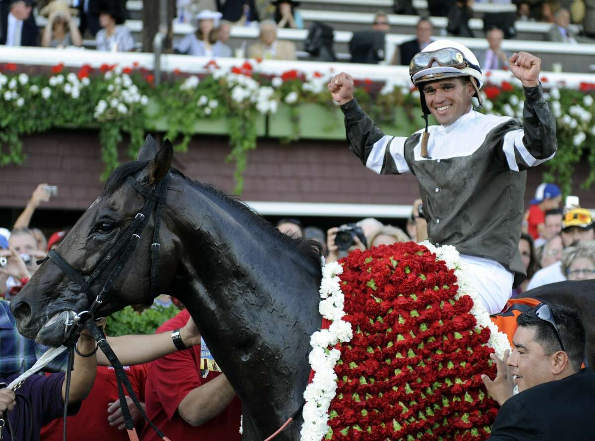 Jockey Javier Castellano raises his hand in victory after Afleet Express won the 141st running of The Travers Stakes won at the Saratoga Race Course in Saratoga Springs this evening August 28, 2010. (Skip Dickstein/Times Union)
