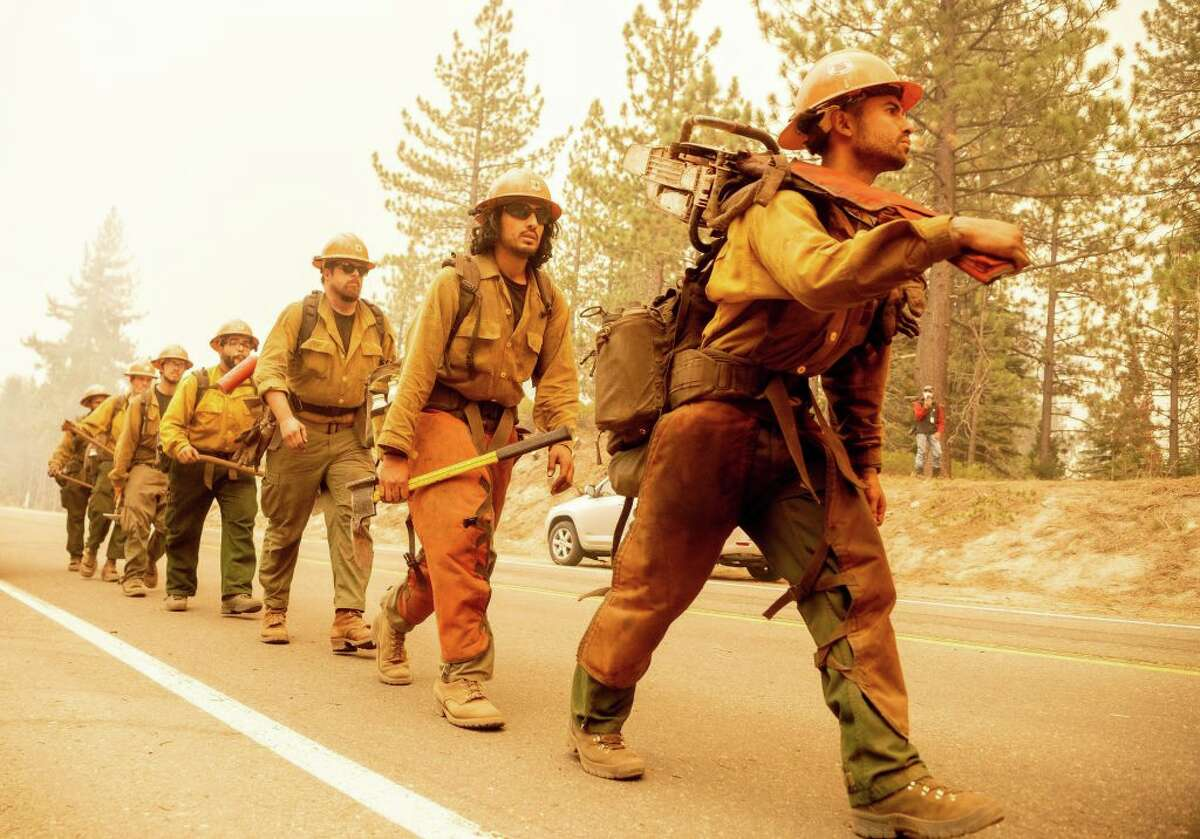 A U.S. Forest Service firefighter crew arrives at the scene where flames from the Caldor Fire threaten to jump Highway 50 in Meyers, Calif., on Aug. 31, 2021.