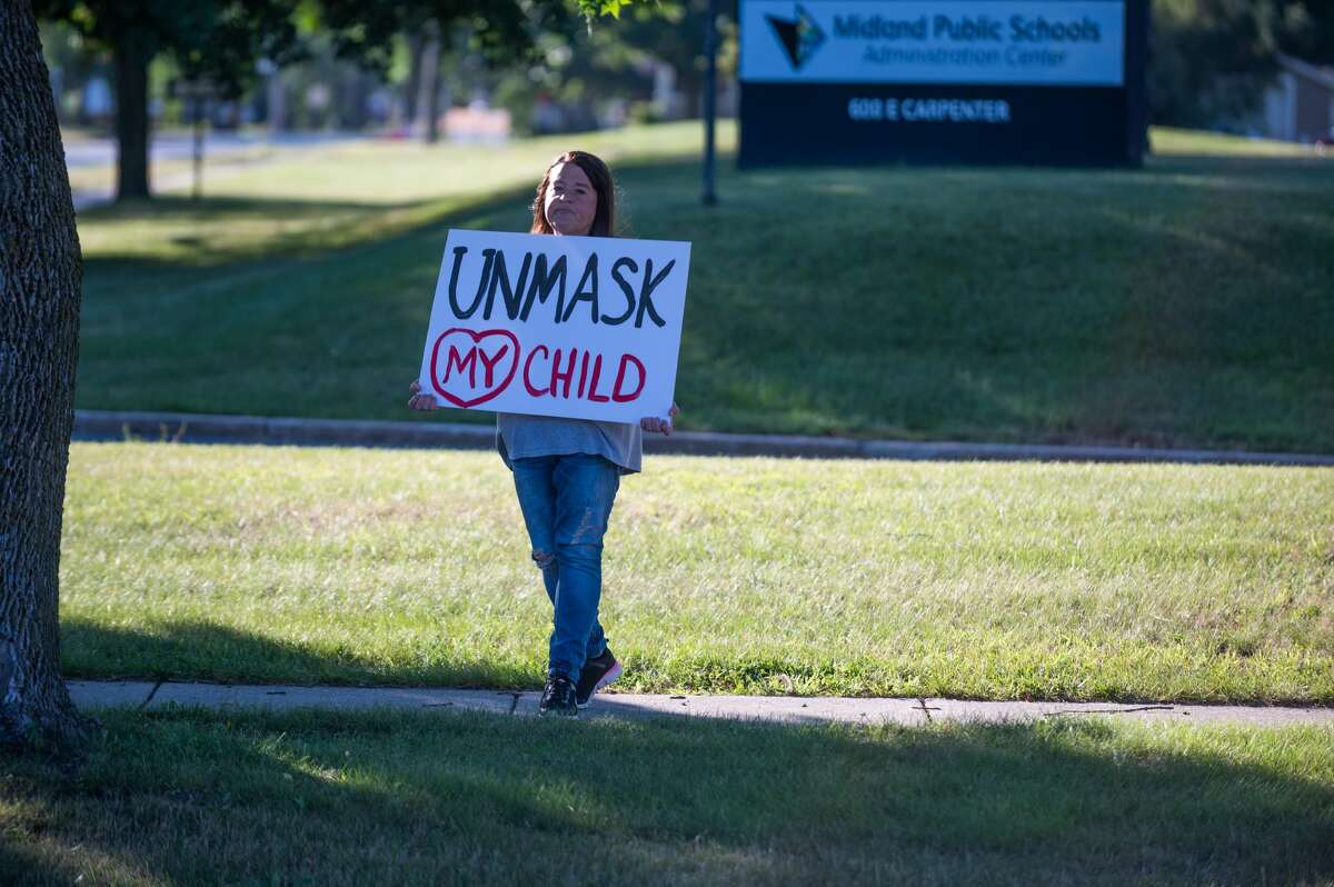 Protesters display signs at the Parents Against MPS Mask Mandate protest at the Midland Public Schools Administration Center on Sept. 1, 2021 (Adam Ferman/for the Daily News)