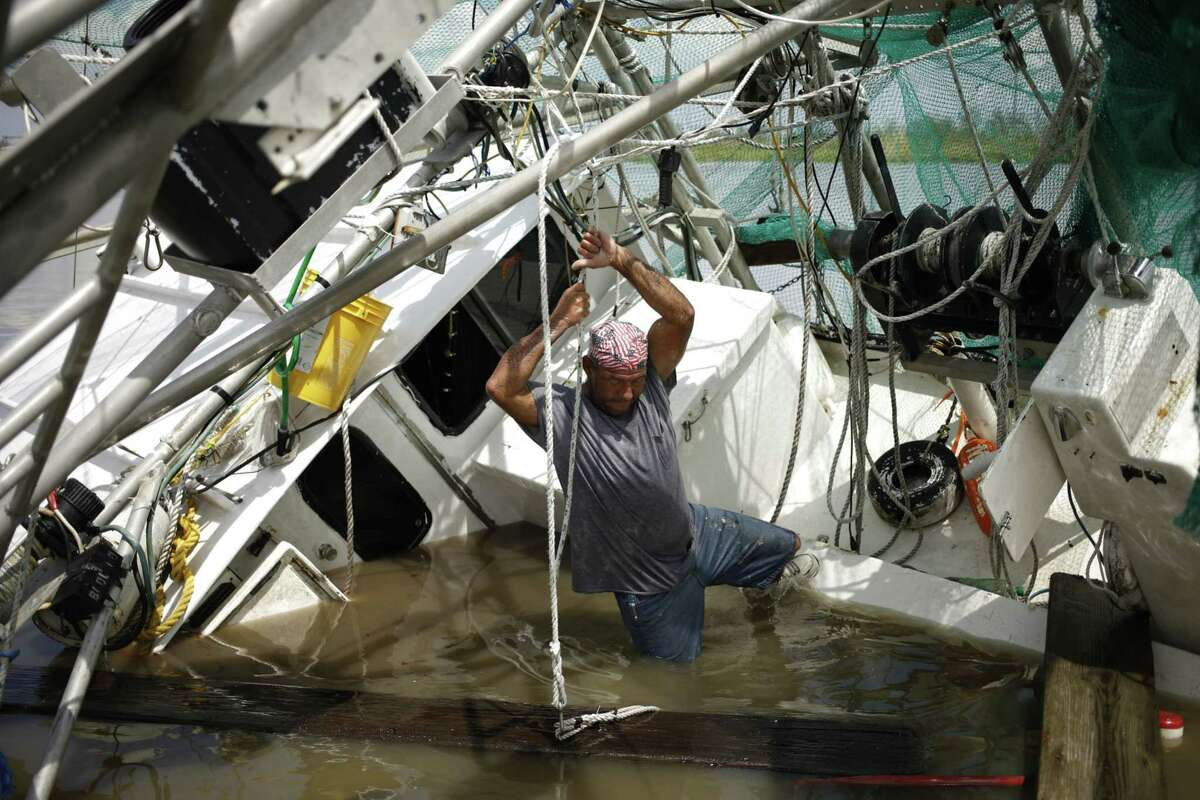A shrimper works to salvage his shrimp boat that was partially submerged by Hurricane Ida in Golden Meadow, La., on Aug. 31, 2021.