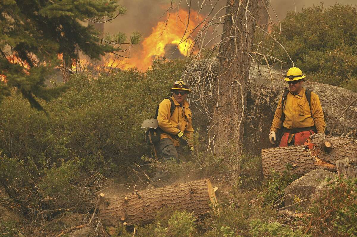 A pair of North Tahoe firefighters use a chainsaw to help remove vegetation that could threaten nearby cabins when the Caldor Fire approaches Tuesday afternoon, Aug. 31, 2021, off of South Upper Truckee Road in California.