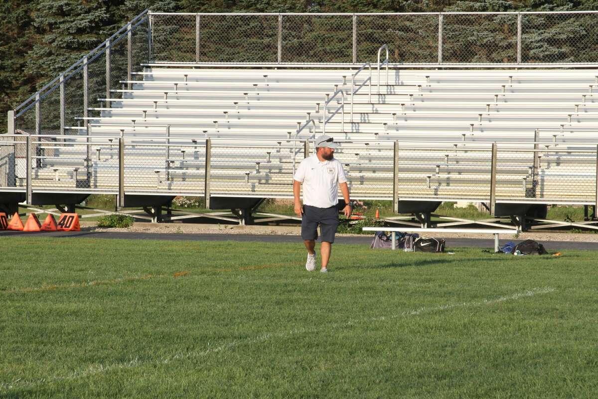 Manistee head coach Brandon Prince walks along the field following a loss to Montague.