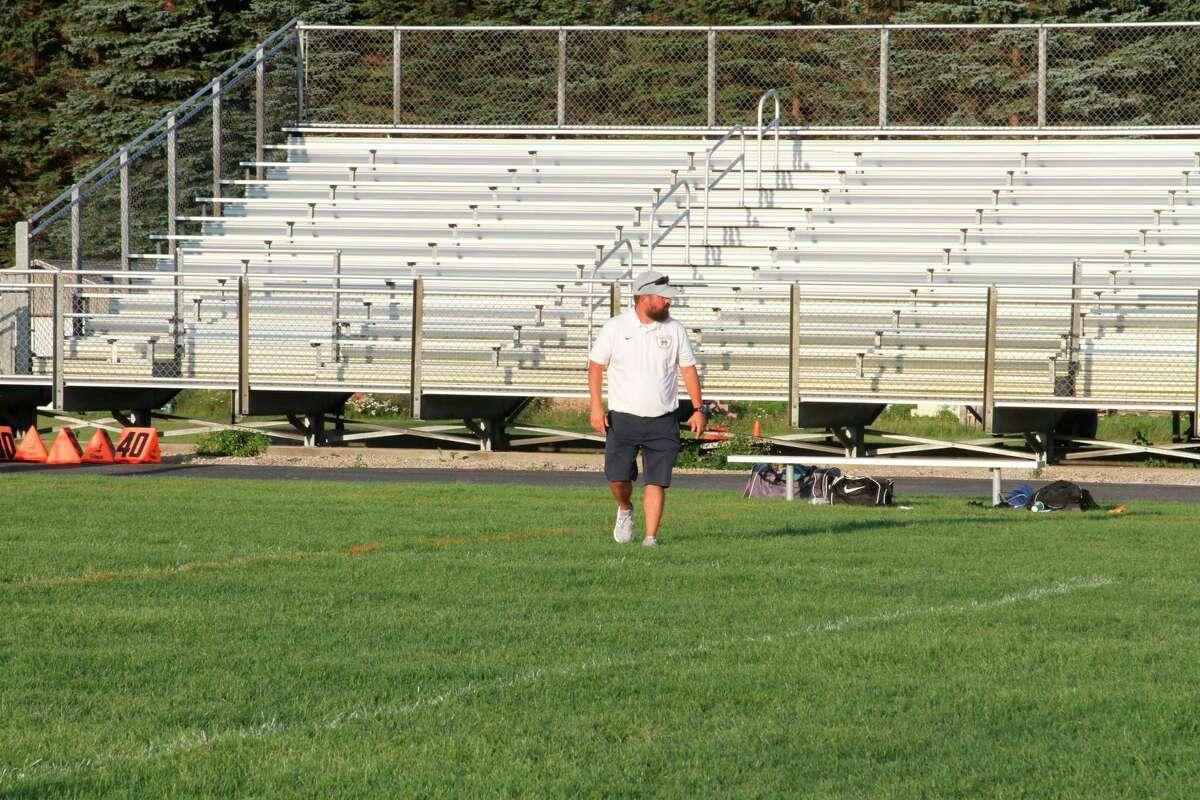Manistee head coach Brandon Prince walks along the field following a loss to Montague. (McLain Moberg/News Advocate)