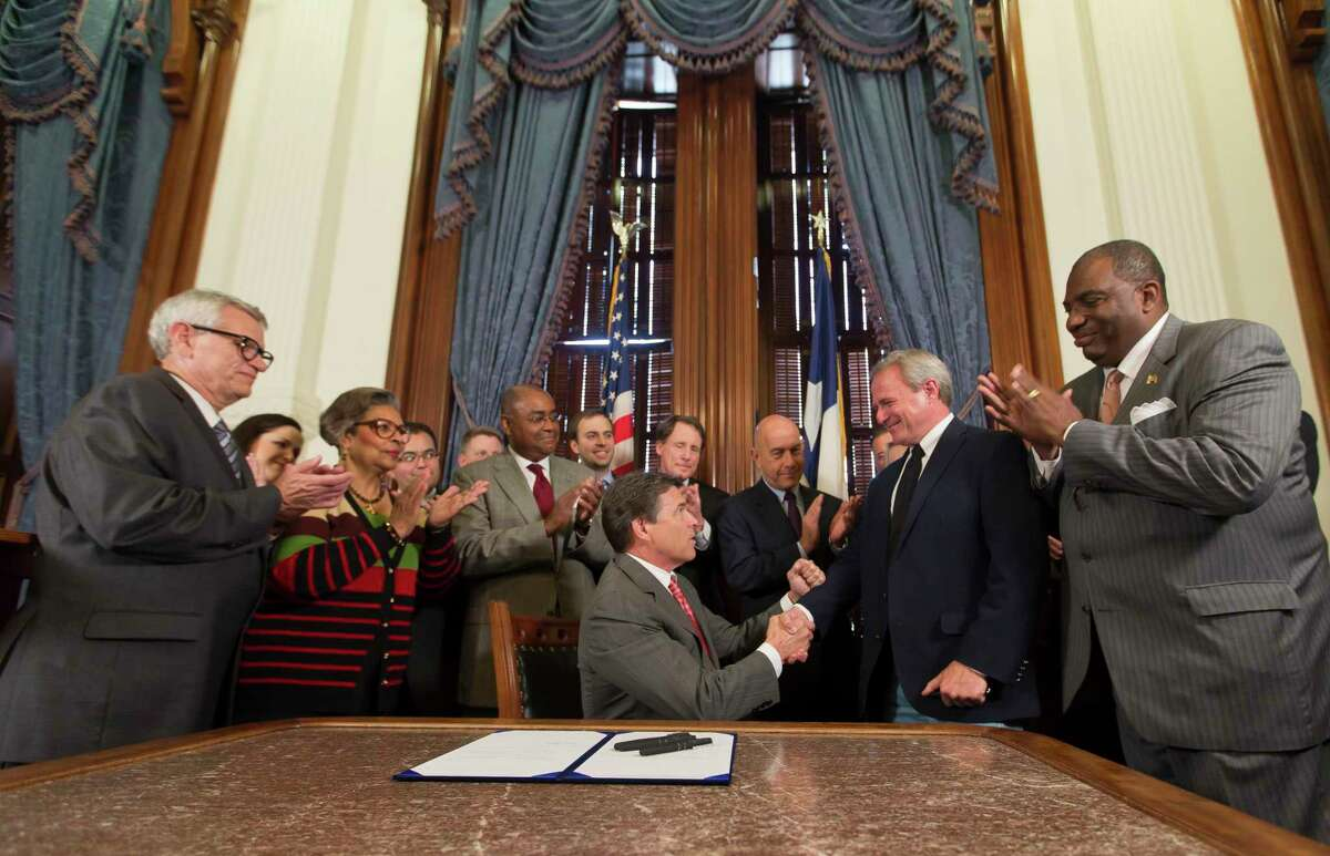 Gov. Rick Perry presents Michael Morton with a pen after signing the Michael Morton Act into law in 2013. A new state law builds on requirements for disclosing evidence.