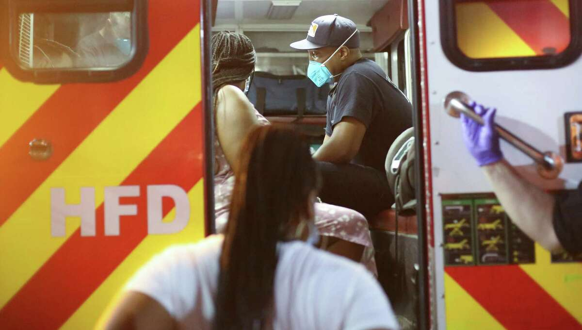 """HFD paramedic Valentin """"Beau"""" Beauliere waits with a patient in the back of an ambulance in Houston on Thursday, Aug. 19, 2021."""
