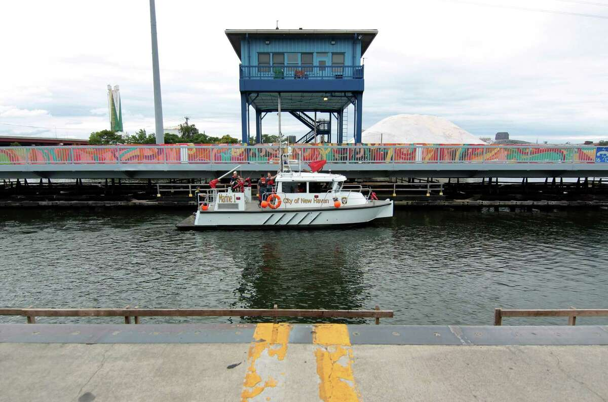 The New Haven Fire Department drops off a crew to diagnose the swing bridge on Chapel Street which malfunctioned and stuck in the open position in New Haven, Conn., on Saturday August 28, 2021.