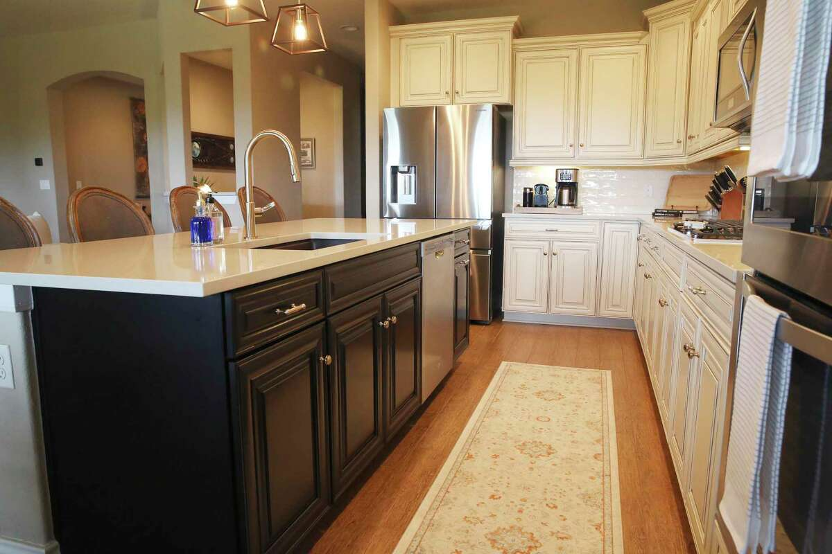 The island cabinets were painted black to contrast with the facing cream-colored cabinets.