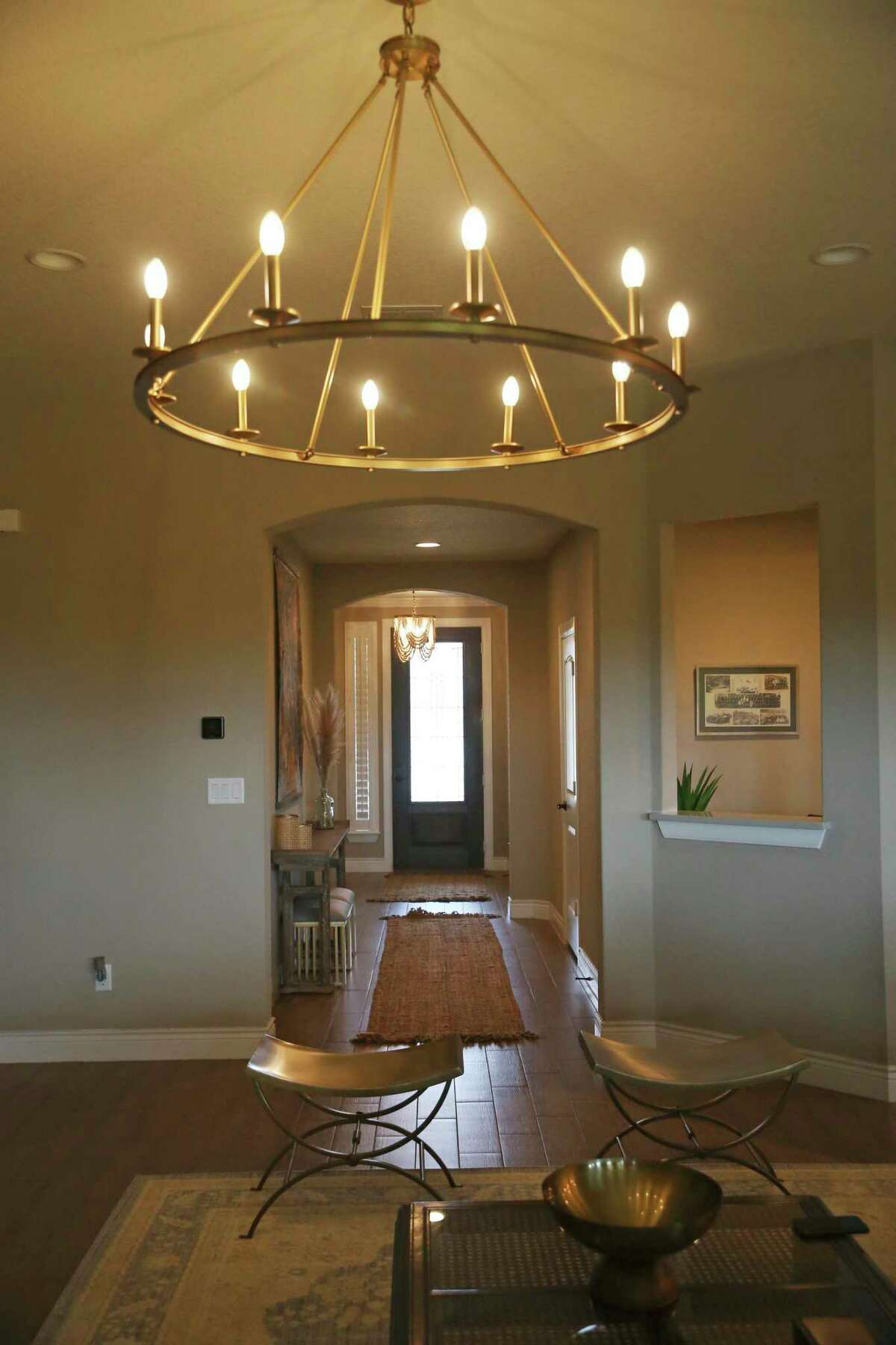 A large circular chandelier with electric candles hangs above the living room seating area.
