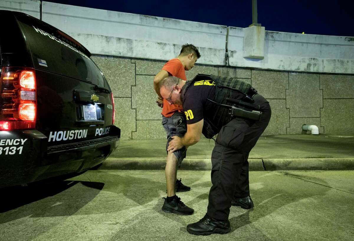 Houston Police tactical officer Peter Ungaro searches a man's shoe while being processed following his arrest on a charge of soliciting prostitution on the Bissonnet Track Thursday, Sept. 6, 2018.