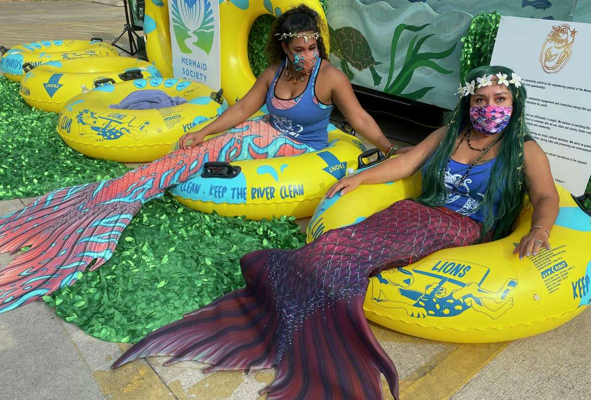 Ayesha Sosa, left, and Marisol Muth, right, pose in inner tubes Wednesday at City Park during a news conference kicking off San Marcos' Mermaid Month.