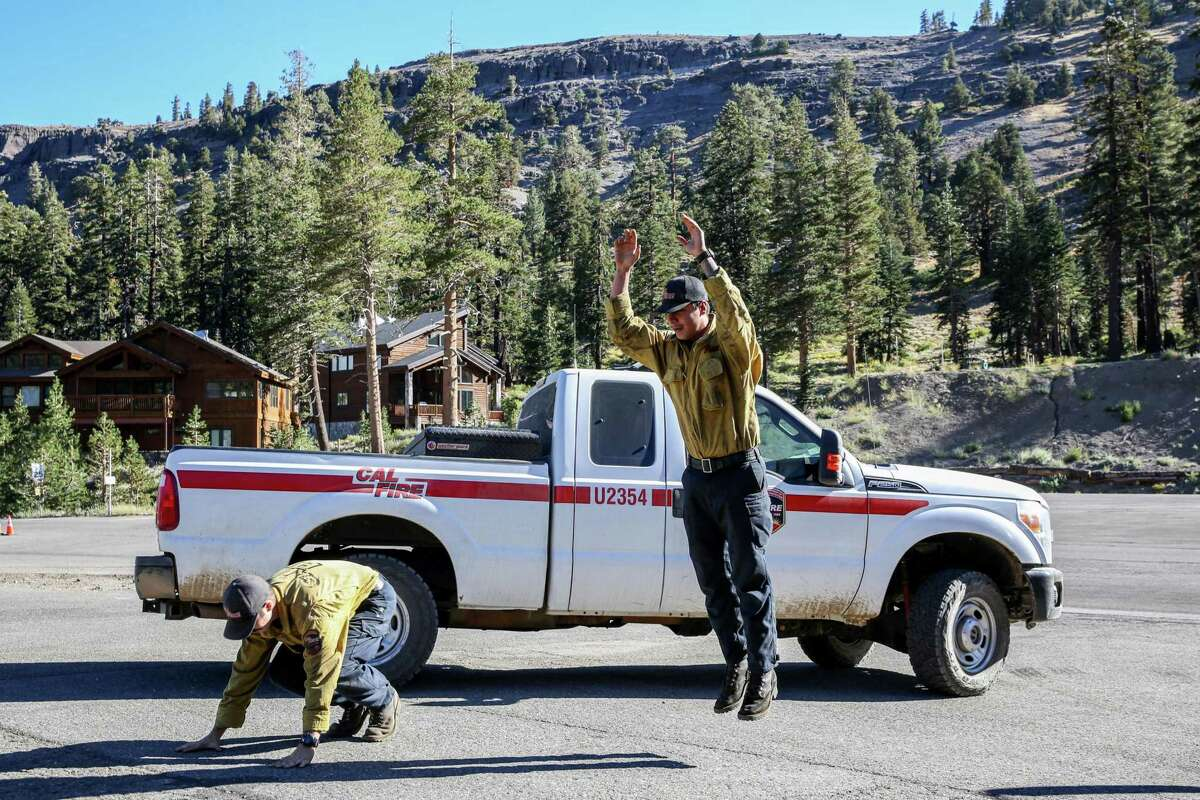 Crew members from Cal Fire Cesar Teran (left) and Matthew Oelrich perform burpees as they wait for orders from their chief while stationed at Kirkwood Mountain Resort. The crews have been fighting the Caldor Fire for several weeks and caught a few moments to break as the smoke cleared, revealing blue skies.