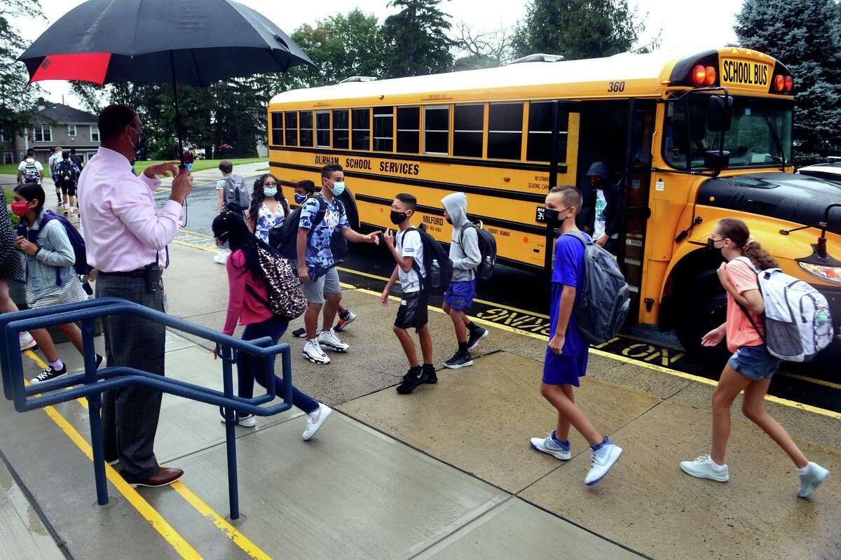 Principal Steve Gottlieb greets students as they arrive for the first day of class at Harborside Middle School, in Milford, Conn. Sept. 1, 2021.