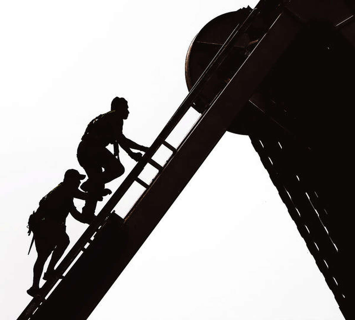Two workers are silhouetted by the hazy skies Tuesday morning as they climb to the center of the Luehrs' giant ferris wheel to start unfolding the sections like the spokes on a bicycle.