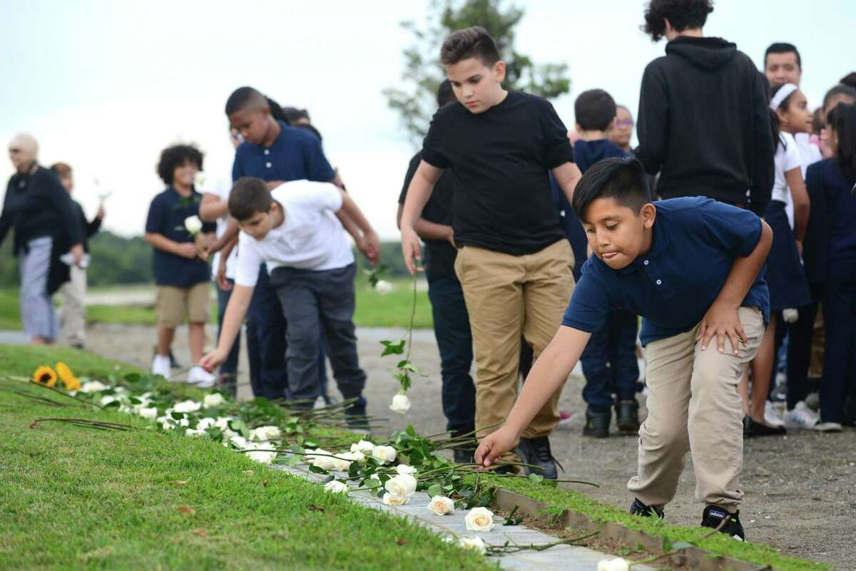 Andres Lopez , 5th grader at Geraldine W. Johnson School in Bridgeporl, lays a rose at the memorial during the State of Connecticut's 18th annual 9/11 Memorial Ceremony honoring and celebrating the lives of those killed in the September 11, 2001 terrorist attacks Thursday, September 5, 2019, at Sherwood Island State Park in Westport, Conn. Family members of those who were killed in the attacks participated, and the names of the 161 victims with ties to Connecticut were read aloud.