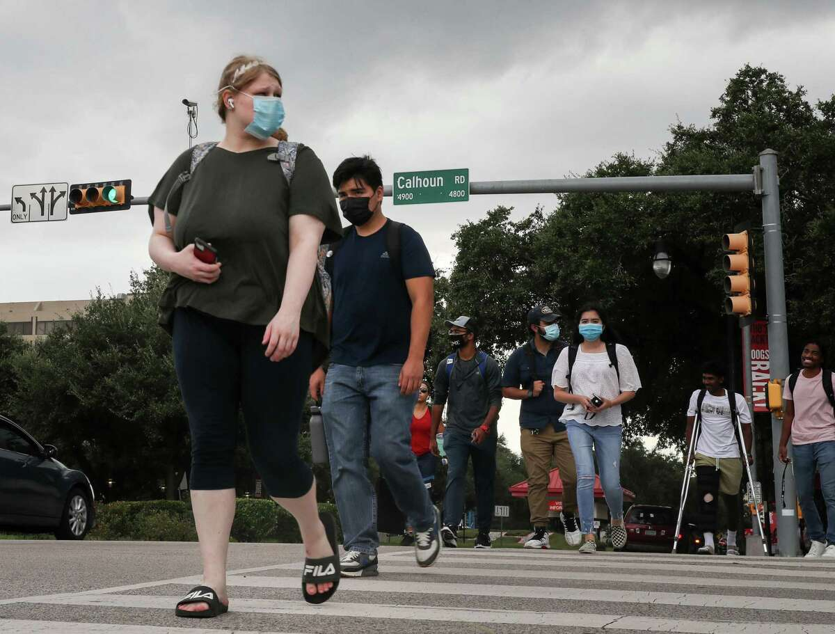 People cross Calhoun Road where it intersects University Drive on Tuesday, Aug. 31, 2021, on the University of Houston campus in Houston. Houston City Council will vote tomorrow to rename part of Calhoun Road to Martin Luther King Boulevard.