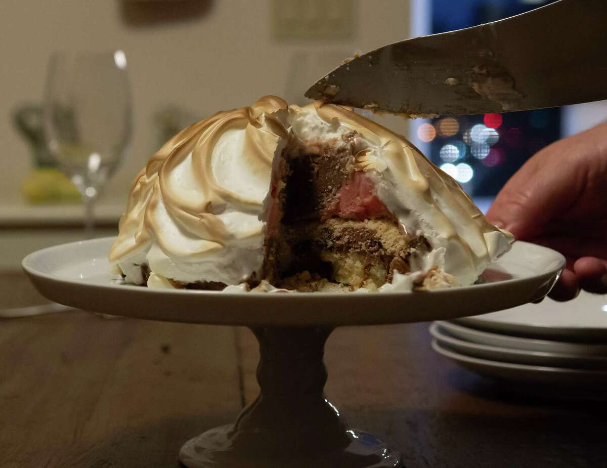 Ralph Elwell cuts a piece of his baked Alaska for his guests at his residence in Saratoga Springs, N.Y. (Jenn March, Special to the Times Union)