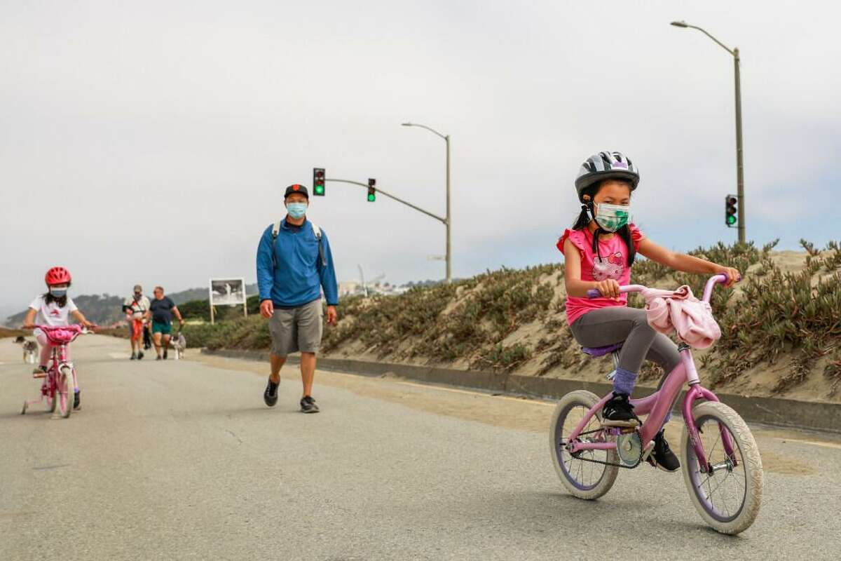 Hazel Ho, 4 father Tung Ho (center) and sister Zoe Ho, 6 (right) ride their bikes and walk on Great Highway on Tuesday, Aug. 10, 2021 in San Francisco, California. This is the last full week of car-free Great Highway. On August 16, it returns to cars five days a week.