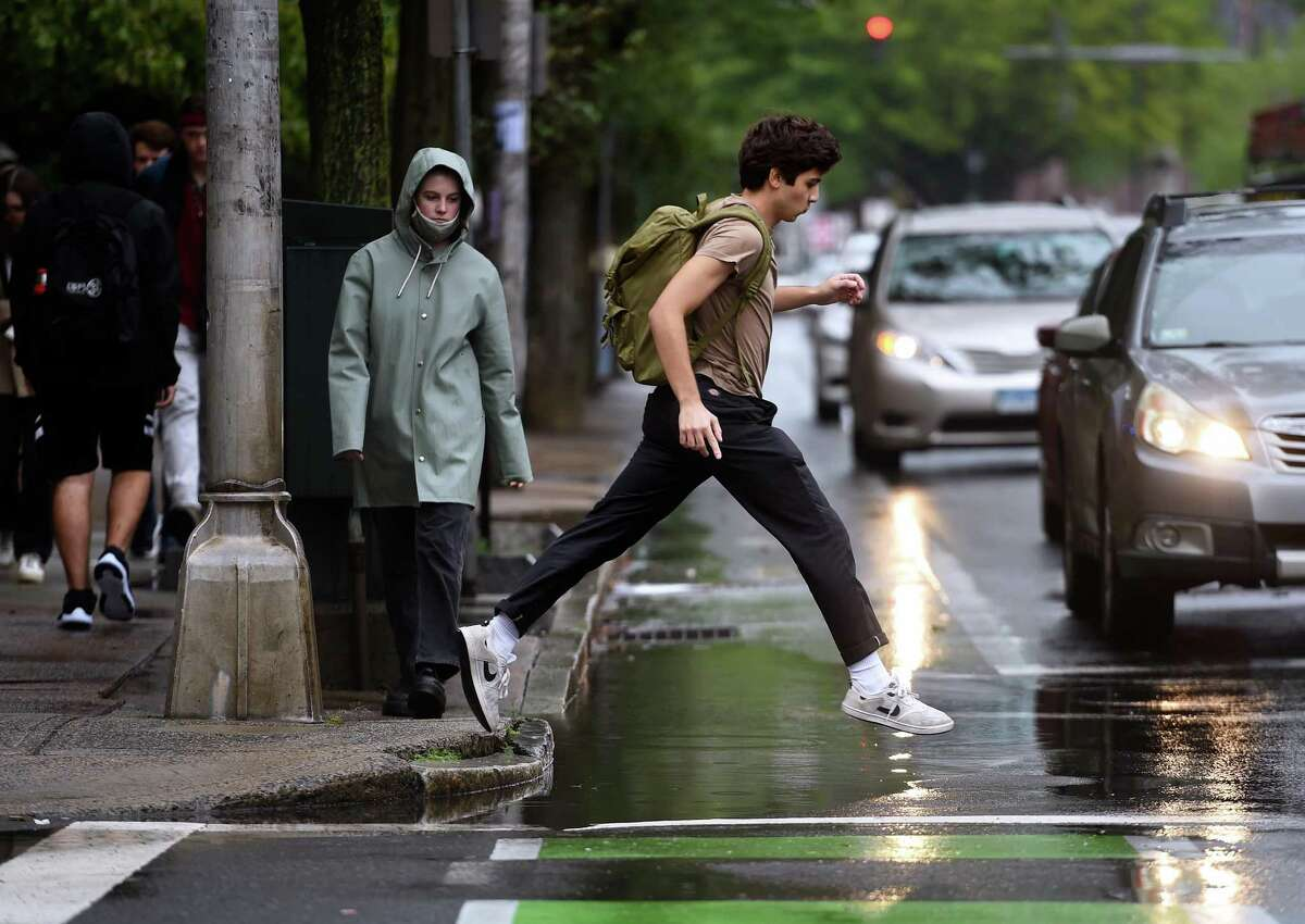 A man navigates a large puddle at the corner of Elm and High Street in the Yale University campus in New Haven on September 1, 2021.