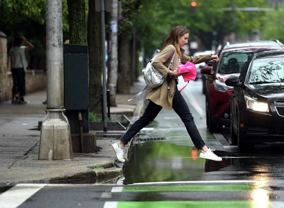 A woman navigates a large puddle at the corner of Elm and High Street in the Yale University campus in New Haven on September 1, 2021.
