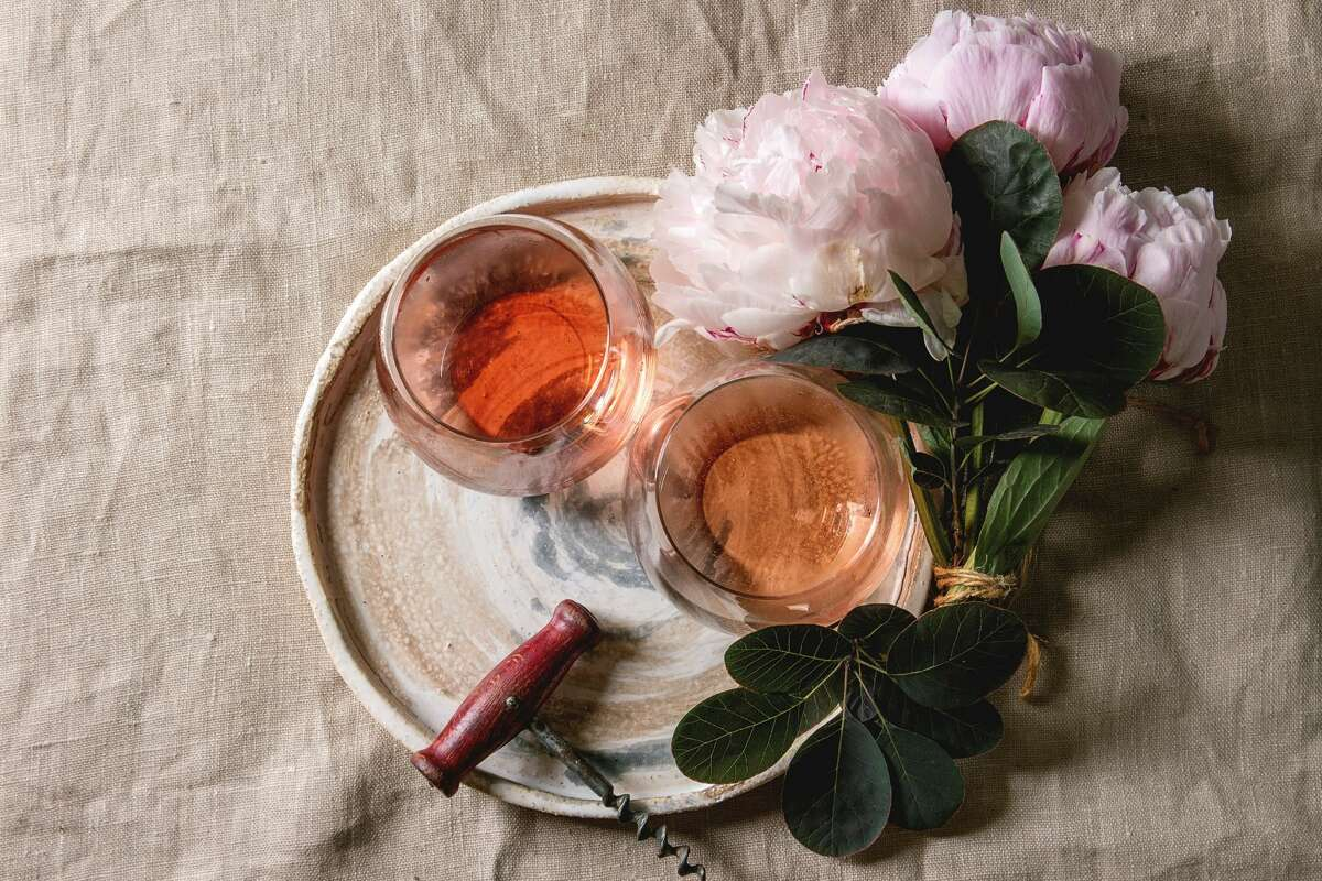 Two glasses of different rose wine standing on grey linen table cloth with pink peonies flowers and vintage corkscrew.