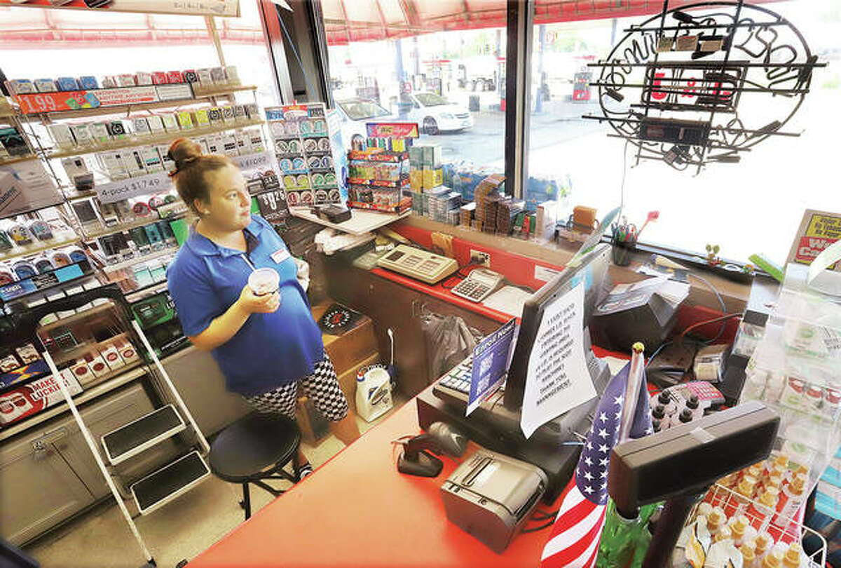 Courtney Davis, a cashier at the Hartford fas-mart convienience store on Illinois 3, waits under the light of the windows Wednesday for the power to come back on. Outages were reported in both Hartford and Alton on Wednesday.