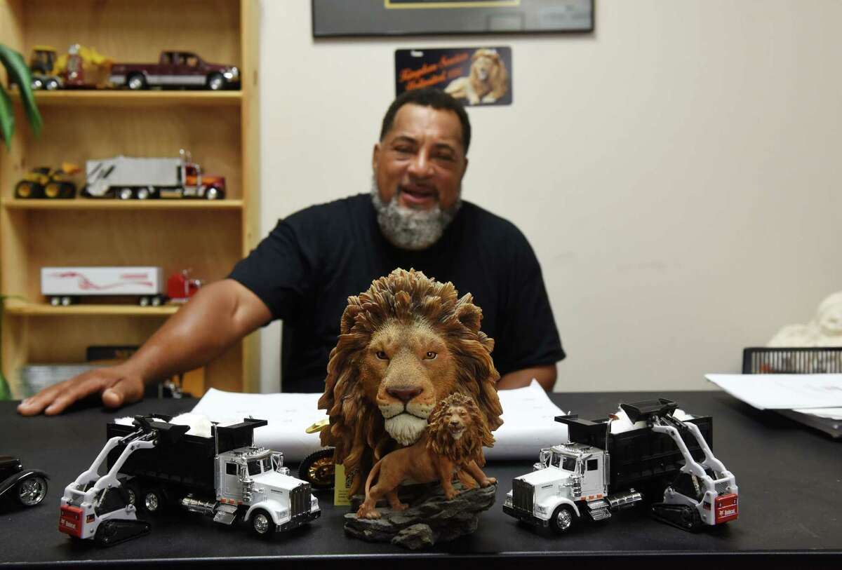John Walker, who owns Kingdom Services, a full-fledge property maintenance service, decorates his desk with models of equipment he would like to own, he also fond of lions, on Wednesday Sept. 1, 2021, at his office in Albany, N.Y. Walker?•s company services over 500 properties.