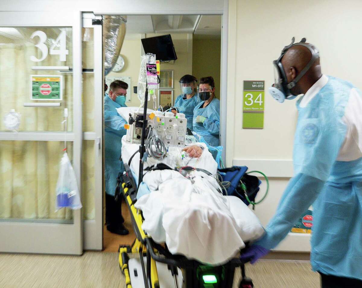 Paramedics transport a COVID-19 patient being admitted into the emergency department at Houston Methodist Hospital on Tuesday, Aug. 24, 2021, in Houston.