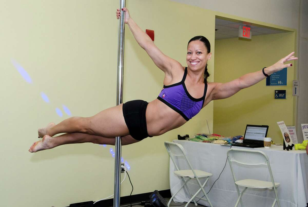 Michelle Abbruzzese, owner of Work It! Dance and Fitness Norwalk, demonstrates pole fitness during the second day of the Health Wellness and Sports Expo 2012 at Chelsea Piers in Stamford on Sunday, Sept. 23, 2012.