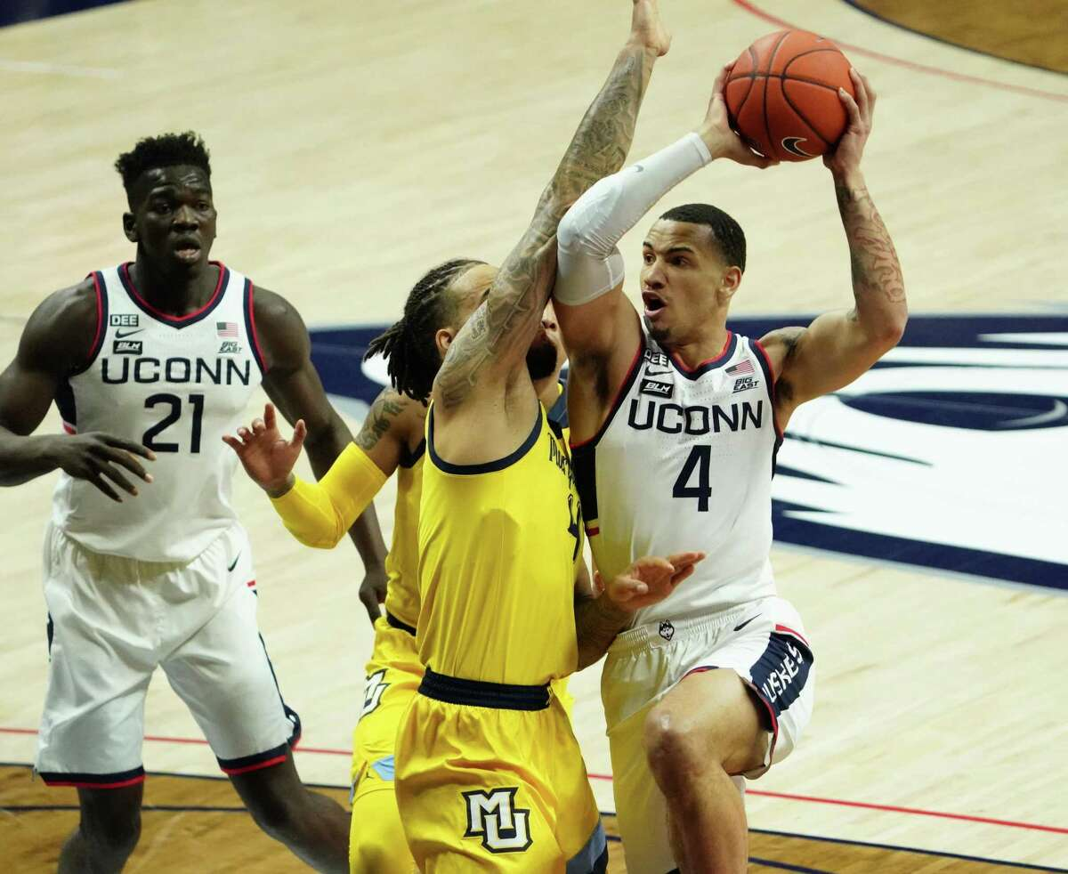 UConn guard Tyrese Martin, right, drives the ball against Marquette forward Theo John during a game in February.