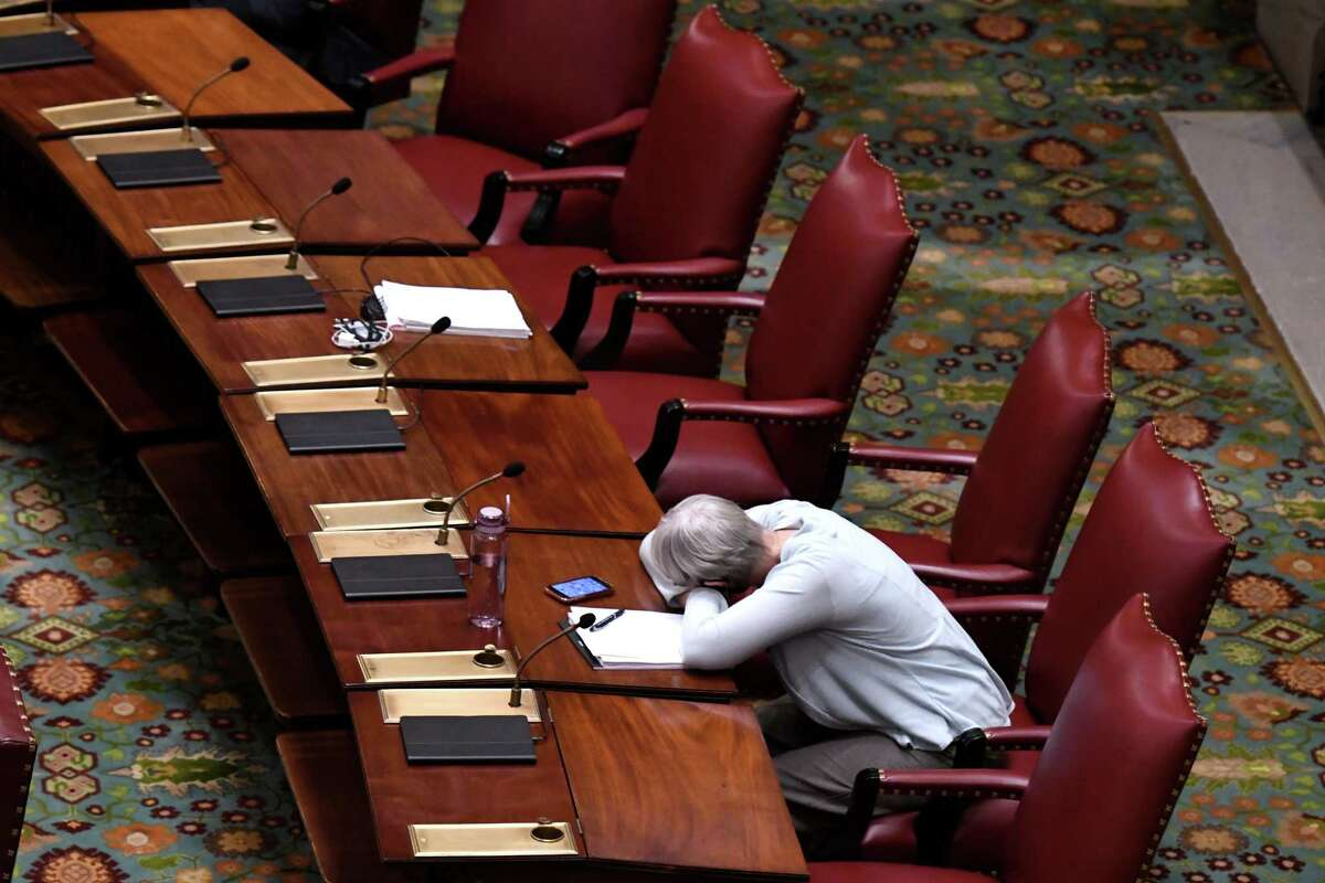 State Sen. Rachel May, (D) 53rd, takes a brief rest on her Senate Chamber desk before the start of a special session on Wednesday Sept. 1, 2021, at the Capitol in Albany, N.Y.