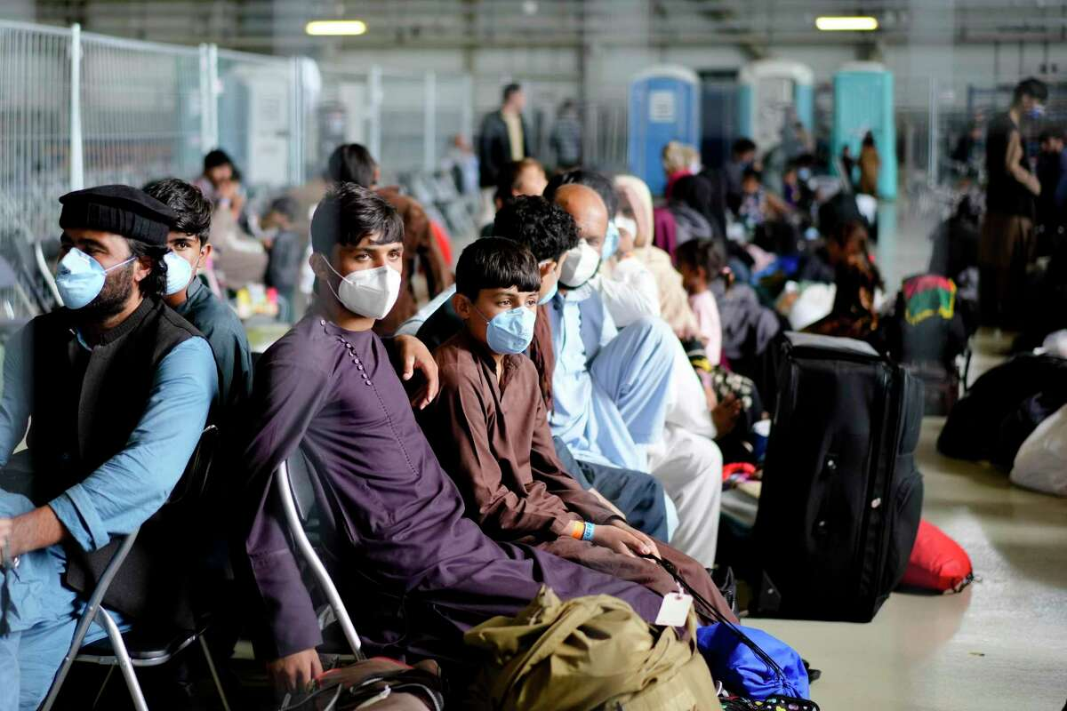Evacuees from Afghanistan wait with other evacuees to fly to the United States or another save location in a makeshift departure gate inside a hanger at the United States Air Base in Ramstein, Germany, Wednesday, Sept. 1, 2021. One of largest American military community overseas gets to a transport hub and houses thousands Afghan evacuees. (AP Photo/Markus Schreiber