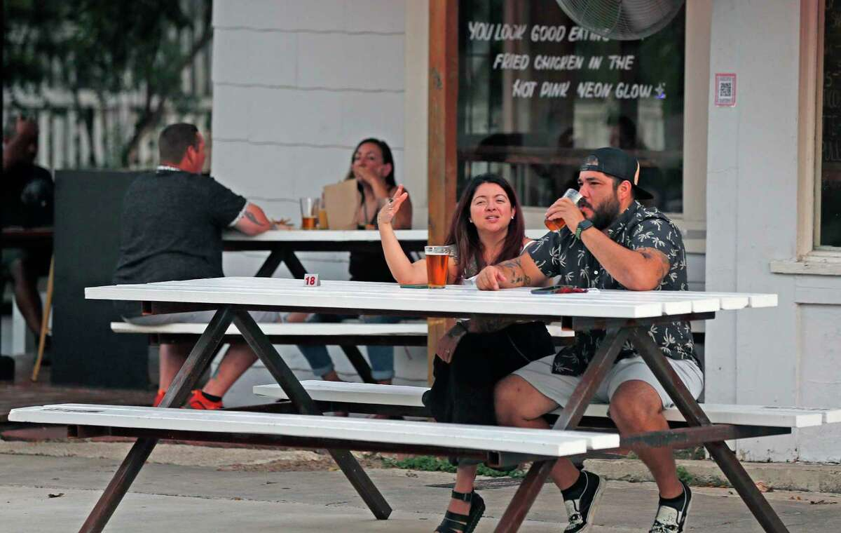 Jesse and Christina Herrera sit at one of the four extra tables placed on the sidewalk outside Cullum's Attagirl Ice House through the city's Eat on the Street program.