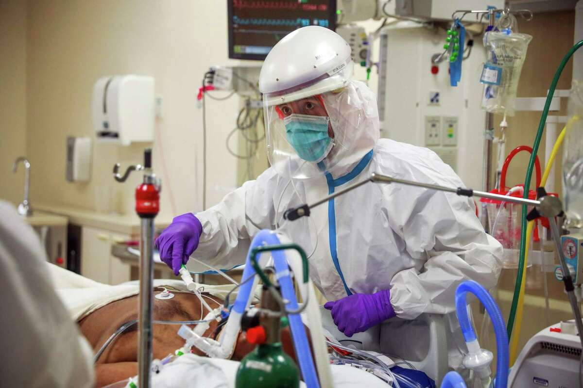 A nurse works in a negative pressure room while taking care of a man with COVID-19 at El Camino Hospital.