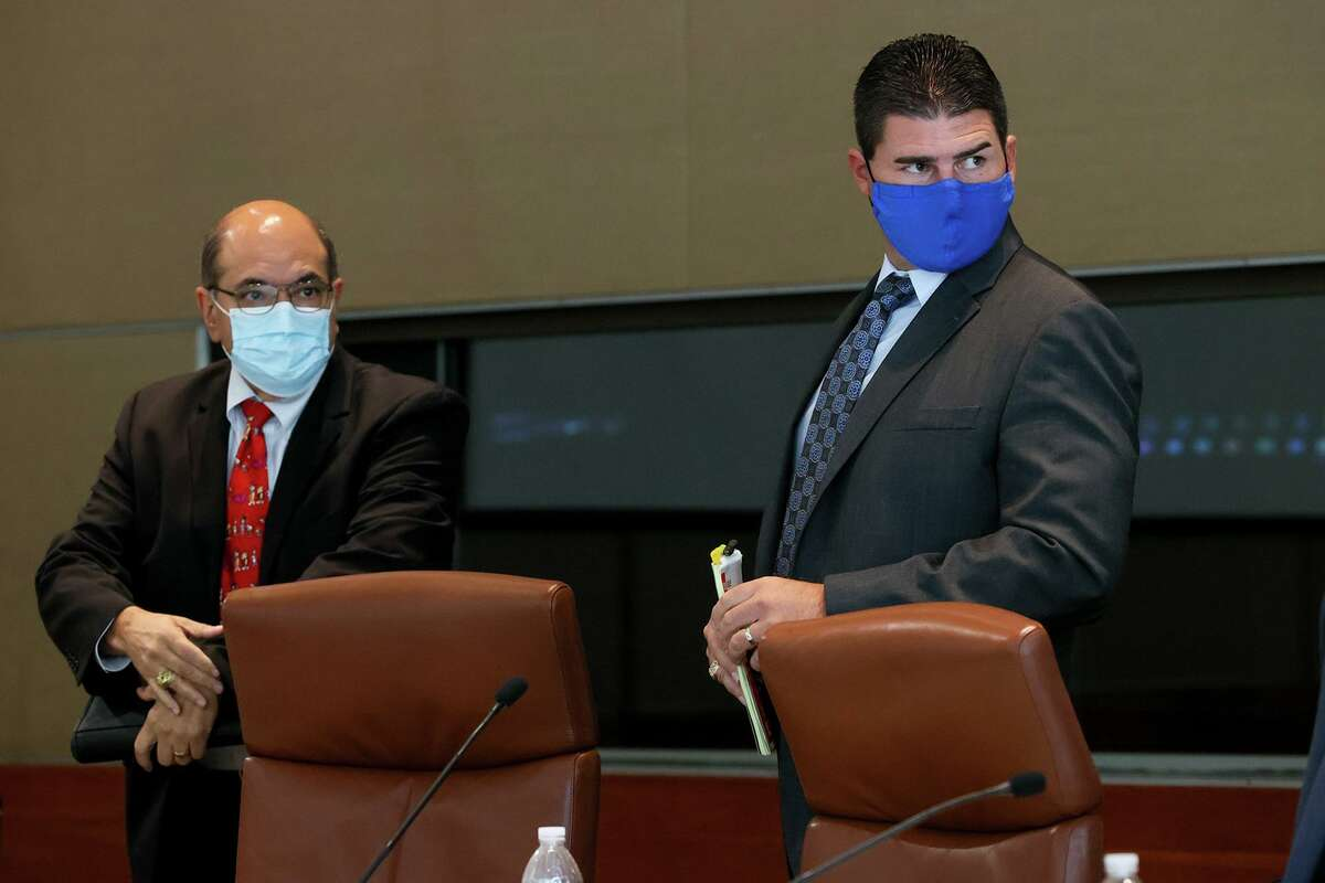 Former San Antonio Police Detective Daniel Pue, right, and his attorney, Morris Munoz, prepare to leave the room for a lunch break on Wednesday during the second day of testimony in an arbitration hearing to determine whether he will be reinstated.