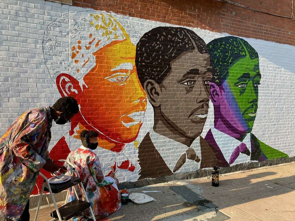 Artist Kwadwo Adae and his son Kwasi Adae work on the elder Adae's latest city mural, this one depicting Yale University graduate Edward Alexander Bouchet, the first African-American doctoral recipient in the United States.