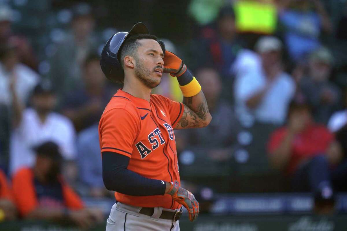 Houston Astros' Carlos Correa stands at home and pulls off his batting helmet after striking out looking against the Seattle Mariners to end the top of the eighth inning of a baseball game Wednesday, Sept. 1, 2021, in Seattle. (AP Photo/Elaine Thompson)