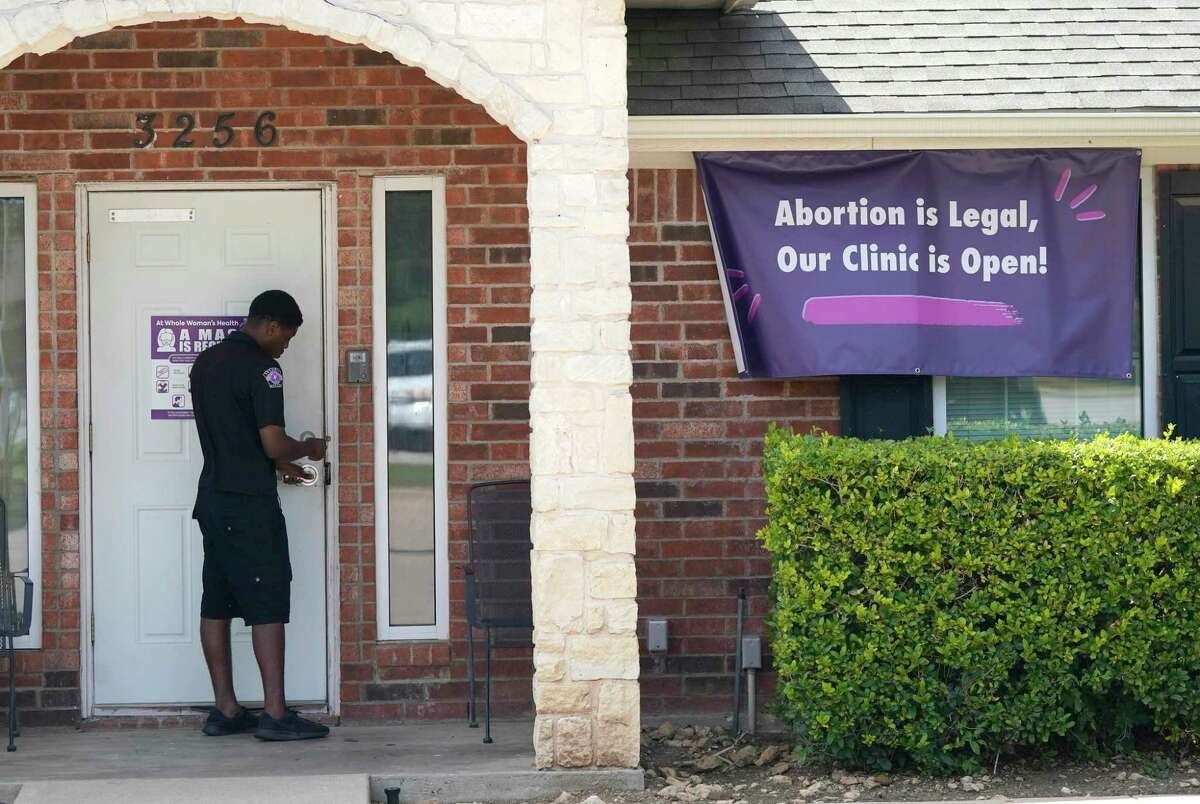 A security guard opens the door to the Whole Women's Health Clinic in Fort Worth, Texas, Wednesday, Sept. 1, 2021. A Texas law banning most abortions in the state took effect at midnight, but the Supreme Court has yet to act on an emergency appeal to put the law on hold. If allowed to remain in force, the law would be the most dramatic restriction on abortion rights in the United States since the high court's landmark Roe v. Wade decision legalized abortion across the country in 1973.