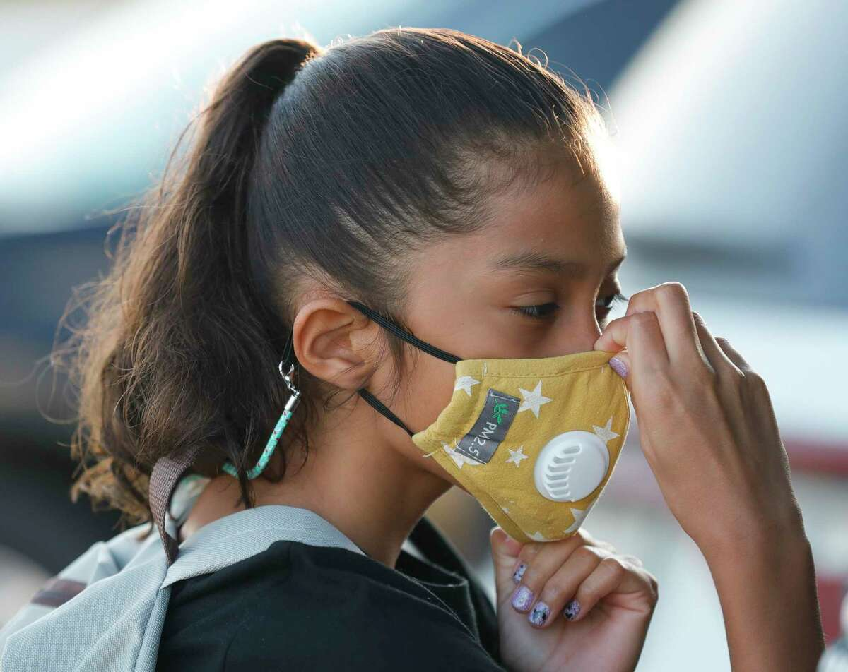 Zoey Gonzalez adjusts her mask before heading into Conroe ISD's new Hope Elementary for the first day of school, Wednesday, Aug. 11, 2021, in Grangerland.