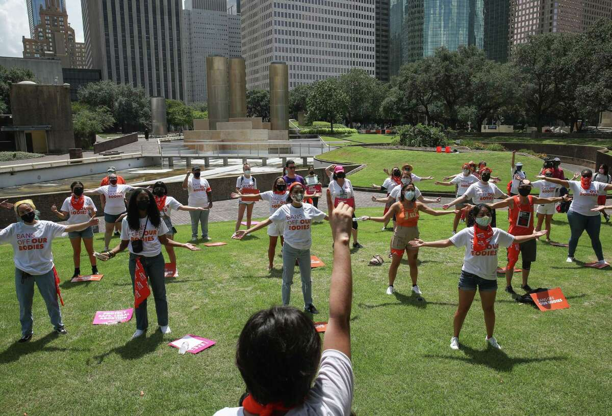 """Vivianna Perez, who works on the outreach and advocacy team of Texas Freedom Network, front center, leads a demonstration against a new Texas law that bans abortions as early as six weeks into a pregnancy, on Wednesday, Sept. 1, 2021, at Tranquillity Park in Houston. The law also empowers private citizens to sue those who defy the law. """"It's going to make access to abortion nearly impossible, and it could potentially cause a domino effect,"""" Perez said of the new law."""