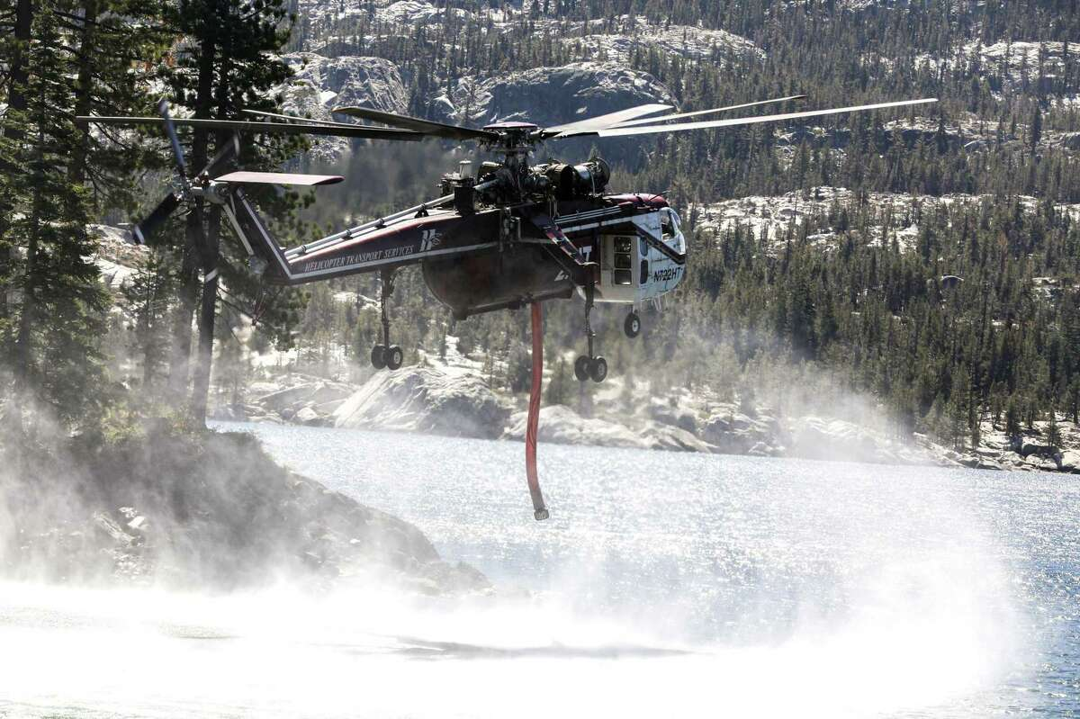 """A helicopter known as a """"Skycrane"""" lowers its draft hose into Silver Lake to gather water to dump on flames from the Caldor Fire."""