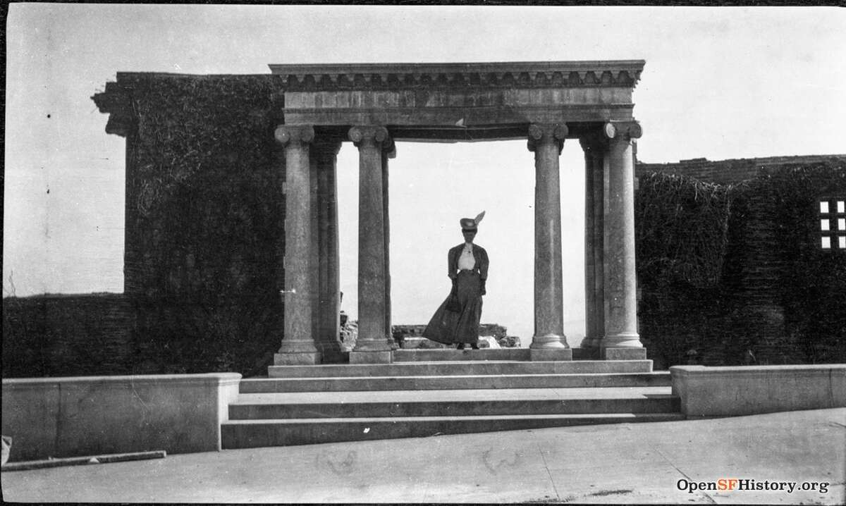 A woman stands under the remaining portico in 1906.